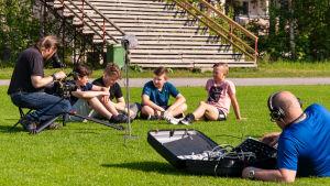 En filminspelning. Fyra pojkar sitter på en fotbollsplan, en fotograf och en ljudtekniker syns också i bild.