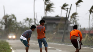 Unga män ute i den hårda vinden i den tyfondrabbade staden Baggao på Filippinerna.