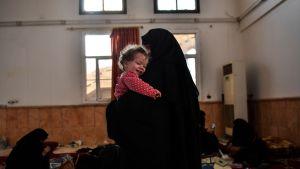 Hustrun till en misstänkt IS-krigare håller sitt barn efter att hon flytt centrum av Raqqa. Bilden är tagen den 8 oktober, då hon väntar på att bli förhörd av SDF.