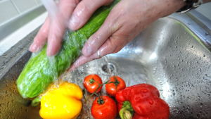 En närbild av händer som tvättar grönsaker under vattenkran.