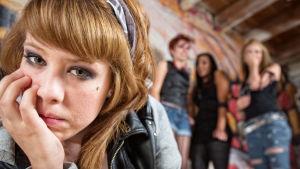 närbild på tonårsflicka som ser in i kameran, hon ser ledsen ut, i bakgrunden står några andra tonåringar.
