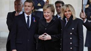 Angela Merkel välkomnas av paret Macron i Paris.