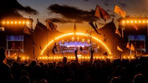 Orangegul stämningsbild på natten på Rokilde-festivalen. Silhuetter av publik med flaggor framför orangea huvudscenen under Eminems gig.