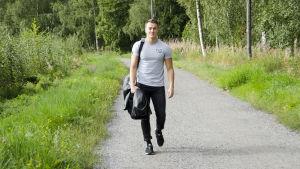 En man iklädd svarta jeans och en grå t-skjorta går på en grusväg kantad med grönt gräs och blommor. Han ler och ser glad ut.
