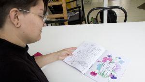 Zarah Holmberg tittar i tidningen hen gjort. I tidningen finns en färgglad teckning på hen och hens bror.