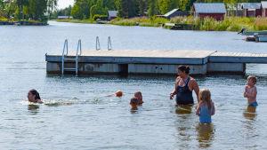 Barn och simskollärare i vattnet invid en brygga.