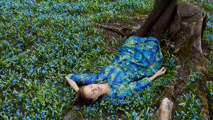 Wilma Hurskaisen teos Blue: Nainen makaa maassa skillojen keskellä
