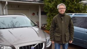 En man står bredvid två bilar.