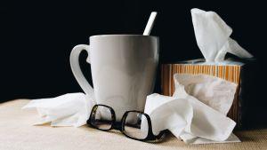 Nenäliinoja, kahvikuppi ja silmälasit pöydällä.
