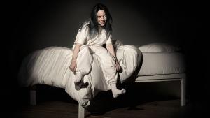 Billie Eilishin debyyttilevyn kansikuva. Naishahmo istuu pimeässä huoneessa sängyn laidalla. Naisella on riivatut silmät.