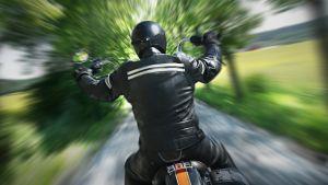 En motorcyklist i svart hjälm och svarta läderkläder sedd bakifrån, kör på en smal väg med träd och grönska på båda sidorna. Skakig bild.