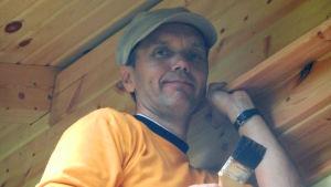 En ung Björn Vikström som står på en stege med målarpensel i handen.