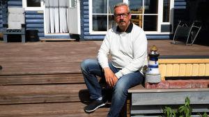 En man sitter på verandan framför en sommarstuga.