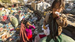 lapsi ja äiti syö kaatopaikalla Kathmandussa Nepalissa