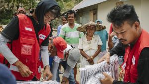 En bild på två personer som sysslar med nödhjälp i Indonesien, de håller i förnödenheter.