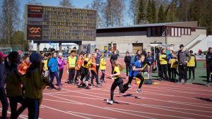 Skolelever springer stafett på en idrottsplan.