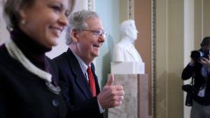 Senatens majoritetsledare Mitch McConnell visade tummen upp då han och hans medarbetare Stephanie Muchow var på väg in i senaten, inför omröstningen.