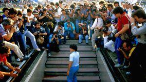 Diego Maradona är på väg upp på stadion och omringas av fotografer.