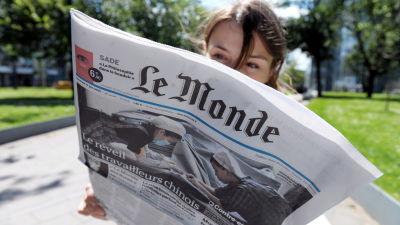 Kvinna läser franska dagstidningen Le Monde.