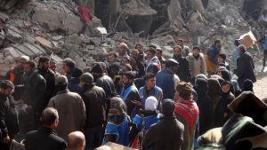 Palestinier väntar på mathjälp i flyktinglägret Jarmuk.