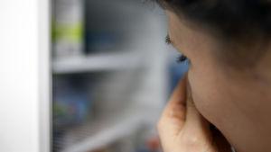 Nainen avaa jääkaapin ja pitelee nenäänsä