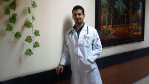 Mieslääkäri työvaatteissaan nojaa seinään ja katsoo kameraan.