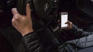 Autoilijan toinen käsi on ratilla ja toinen käyttää älypuhelinta.