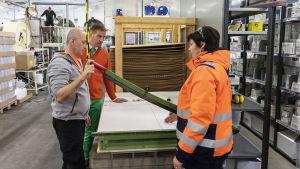 Kolme henkilöä keskustelemassa tuotantolaitteen äärellä.