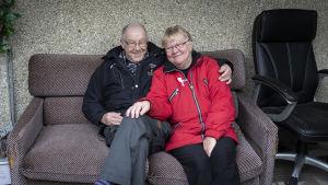 Ikääntynyt pariskunta lähekkäin sohvalla. Molemmat hymyilevät.