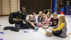 Vasemmalla kitaraa soittava Malloy Nyakwama ja hänen oikealla puolellaan erilaisia instrumentteja soittavia lapsia.