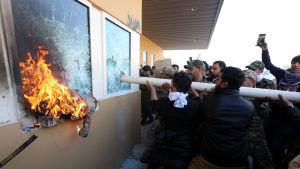 En folksamling krossar fönster på en byggnad med en stång. Ett trasigt fönster brinner.