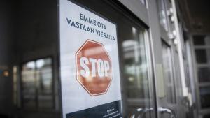 Vieraat kieltävä kyltti Pohjois-Karjalan keskussairaalan ulko-ovissa.
