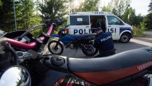 En polis lossar en registerskylt från en moped.