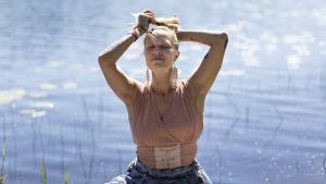 Fredrika Winsten istuu vesistön äärellä silmät suljettuina ja kieputtaa käsillään pitkiä vaaleita hiuksiaan nutturalle.