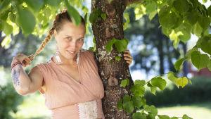Fredrika Winsten pitää kiinni puun rungosta vasemmalla kädellään. Toinen käsi pitää kiinni letistä. Fredrika katsoo kameraan ja hymyilee itsevarmasti.
