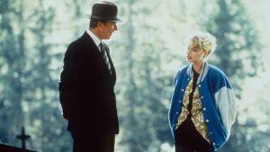 En scen från Änglagård: Sven Wollter i kostym och hatt står bredvid Helena Bergström i blå jacka.