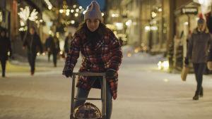 På bilden ses skådespelaren Ida Elise Broch i rollen som Johanne. Hon är klädd i rutig jacka och mössa och åker på en sparksläde i en vintrig småstad.
