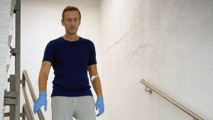 Den ryske oppositionspolitikern Aleksej Navalnyj går ner för trappor iklädd gummihandskar, t-skjorta och mjuka byxor på det tyska sjukhus där han vårdades efter giftattacken i Ryssland i augusti 2020.