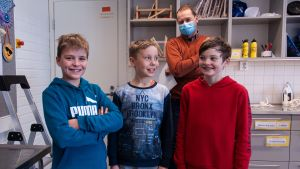 Tre leende pojkar poserar för kameran, i bakgrunden en vucen man med munskydd.