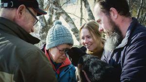 Unelma Lapista -sarjan Annamari, hänen puolisonsa ja isänsä katsovat, kuinka koiranpentu nuuhkii Annamarin äidin kasvoja.