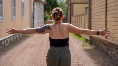 En kvinna går på en gata med trähus med armarna utsträckta.