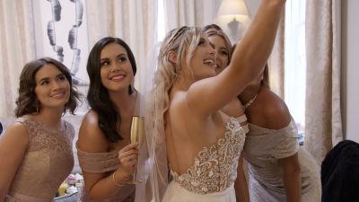 En grupp kvinnor i bröllopsklänningar tar en selfie.