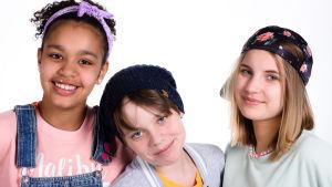 Tre barn som ler till kameran