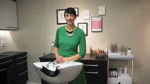 En kvinna med kort svart hår, och grön klänning, står vid ett tvättfat för hårtvätt.