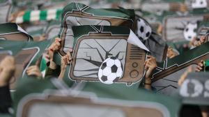 Affischer med trasiga teverutor och en fotboll mot rutorna lyfts upp i ett stort hav av händer.
