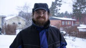 En man står utomhus. Det är vinter med snö på marken.