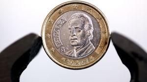 En tång håller i ett spanskt eneurosmyn med texten España och en bild på en man.