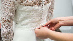 Händer knäpper igen en brudklänning i ryggen.