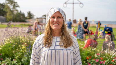 En kvinna iklädd randig pyjamasdräkt med en tomteliknande luva i samma tyg.