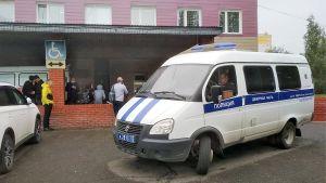 Poliisin pikkubussi seisoo sairaalan edessä. Äsken on satanut, auton alla on kuiva kohta,